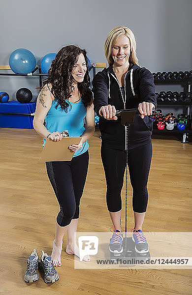 An attractive middle-aged woman standing on the scale for her personal trainer after working out at the fitness facility  Spruce Grove  Alberta  Canada