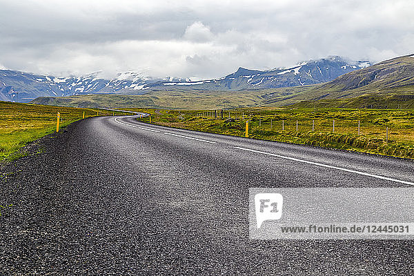 The open highway leads into the mountain landscape in Western Iceland  Iceland