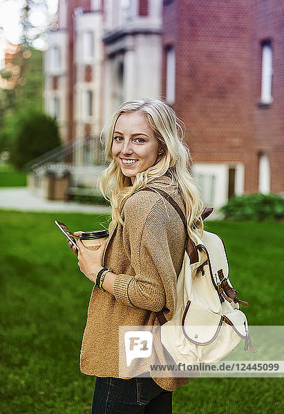 A beautiful young woman with long blond hair holding a coffee cup and texting on her smart phone while walking in a university campus stops to pose for the camera  Edmonton  Alberta  Canada