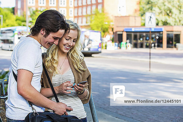 A young couple stands near a bus stop on the university campus looking at a smart phone  Edmonton  Alberta  Canada