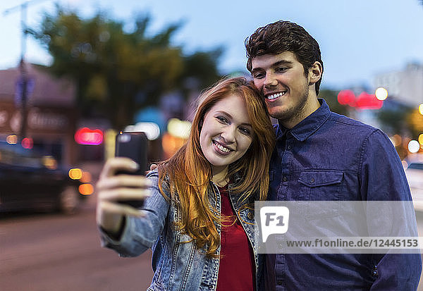 A young couple stand beside a city street at dusk taking a self- portrait with a smart phone  Edmonton  Alberta  Canada