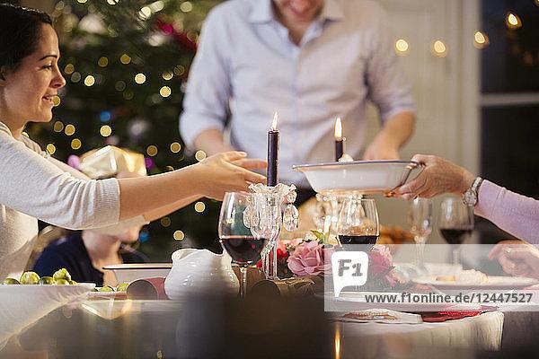 Family passing food  enjoying candlelight Christmas dinner
