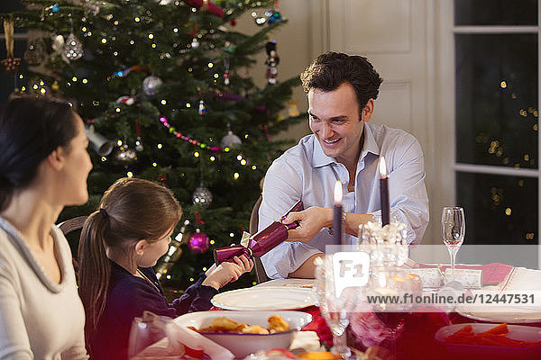 Father and daughter pulling Christmas cracker at candlelight dinner table