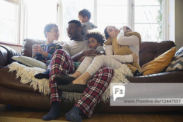 Young family relaxing in pajamas on living room sofa