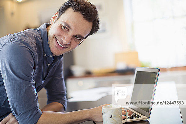 Smiling  confident man working at laptop in kitchen