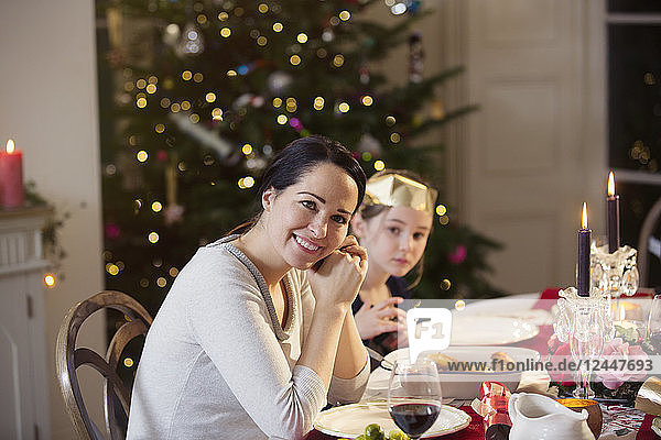 Portrait smiling mother and daughter enjoying candlelight Christmas dinner