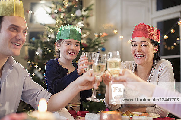 Happy family in paper crows toasting water and champagne glasses at Christmas dinner