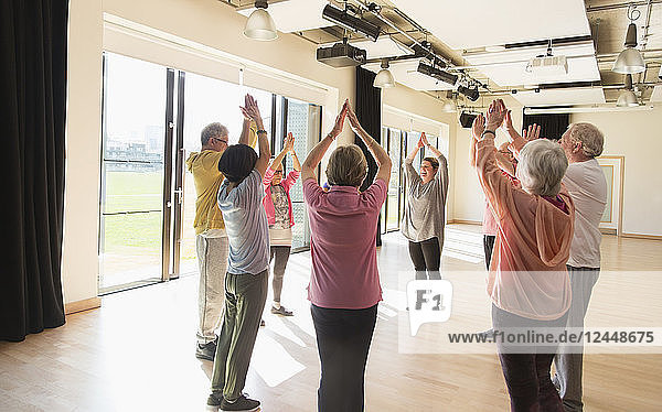 Active seniors exercising  stretching arms overhead in circle