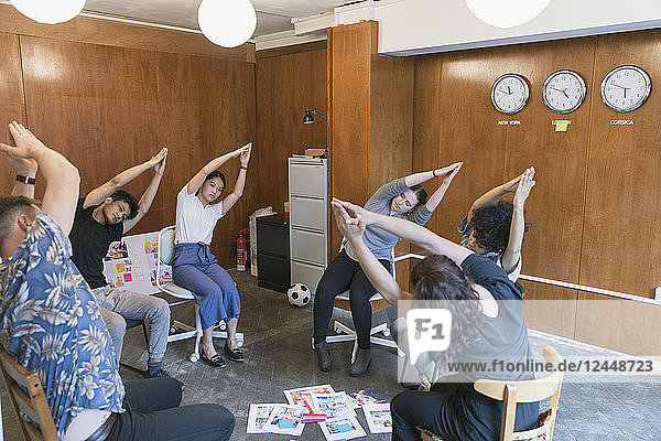 Creative business people stretching  taking a break in meeting