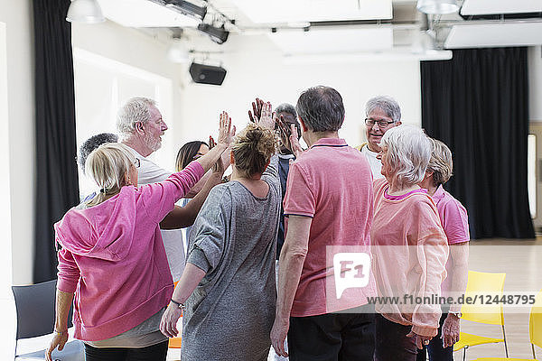 Active seniors high-fiving in circle huddle