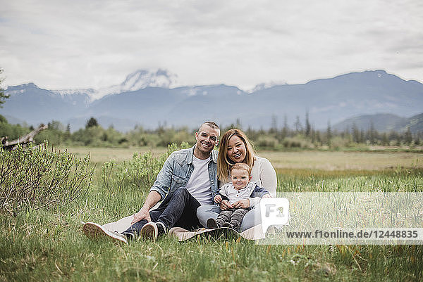 Portrait smiling parents and baby son sitting in rural field with mountains in background