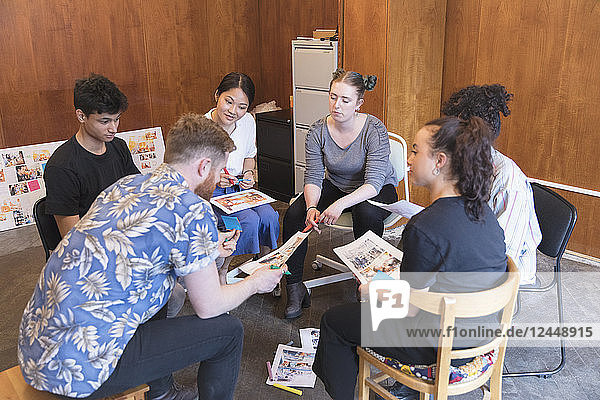Creative designers reviewing proofs in office meeting