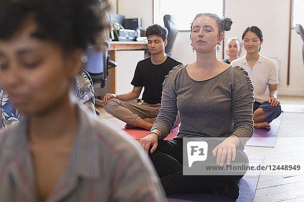 Serene creative businesswoman meditating in office