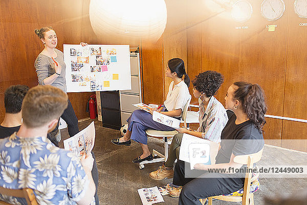 Creative designers brainstorming  reviewing photograph proofs in office meeting