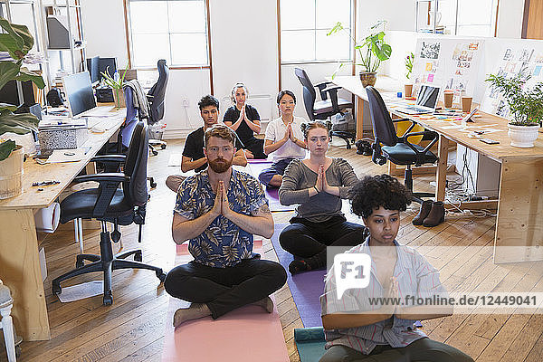 Creative business people meditating in office