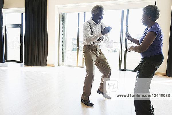 Playful active senior couple dancing in dance studio
