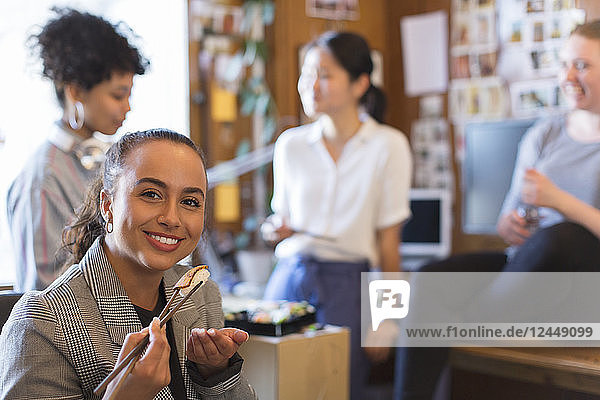Portrait smiling  confident creative businesswoman eating sushi in office