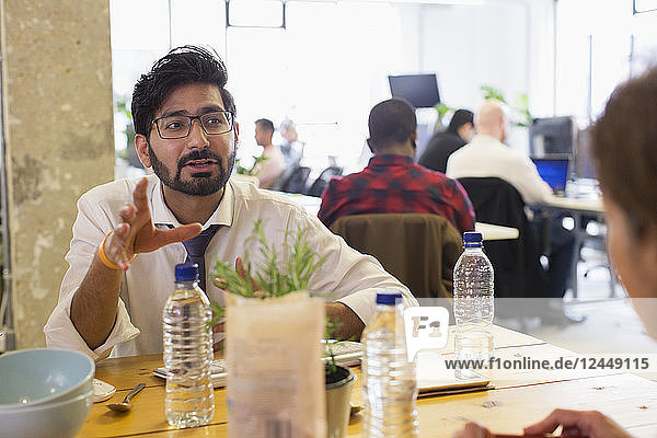 Businessman talking with colleague at lunch table in office