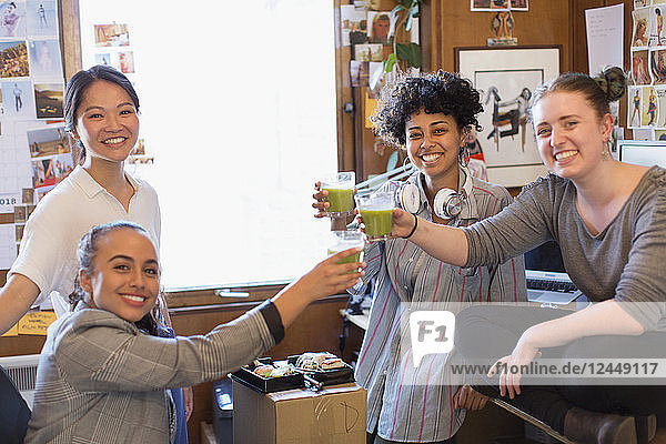 Portrait confident creative female designers drinking green smoothies in office