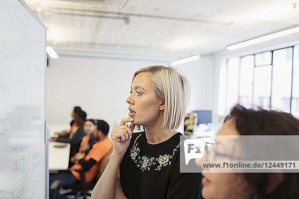 Focused businesswomen brainstorming at whiteboard in office