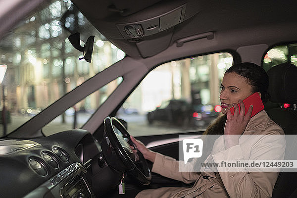 Businesswoman talking on smart phone in car at night Businesswoman talking on smart phone in car at night