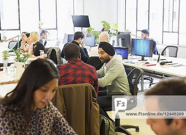 Computer programmers working in open plan office