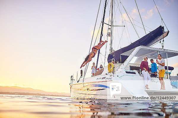 Young woman diving off catamaran into ocean Young woman diving off catamaran into ocean