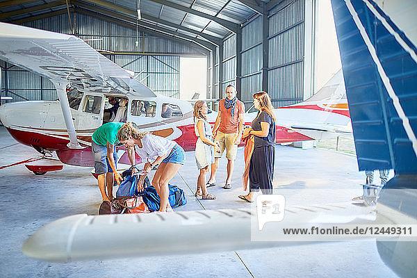 Friends preparing bags in airplane hangar