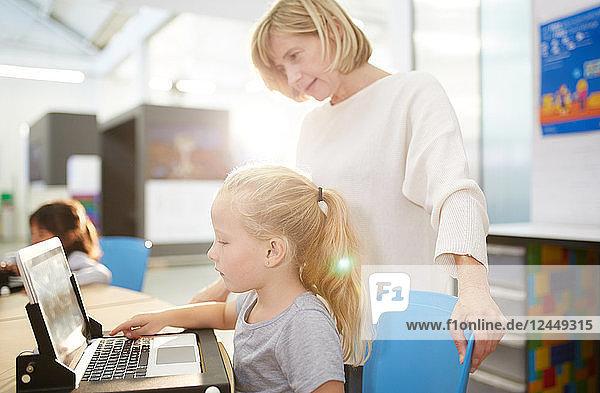 Teacher and schoolgirl using laptop in science center