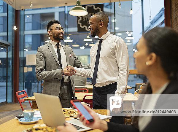 Businessmen handshaking  working in cafe