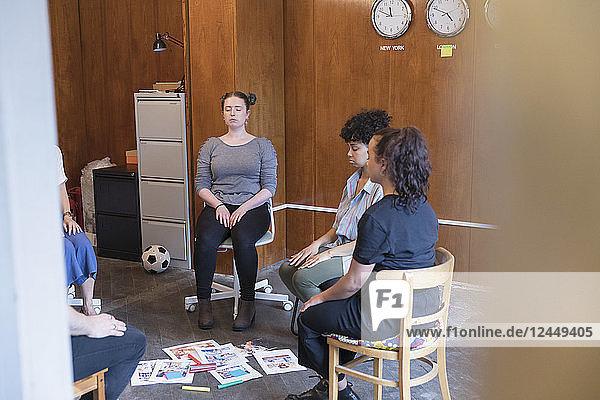 Serene  creative businesswomen meditating in circle  taking a break in meeting