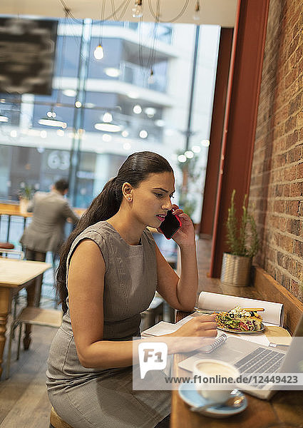 Businesswoman talking on smart phone  working at laptop in cafe