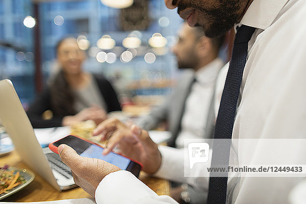 Close up businessman using smart phone in cafe