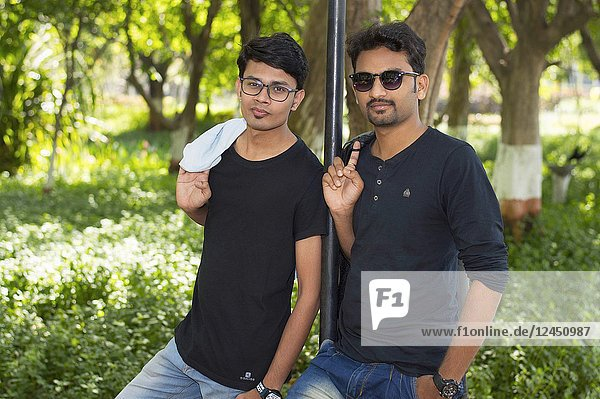 Two handsome young men in casual trendy clothes looking at camera.