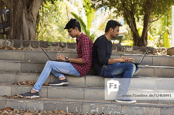 Young students using laptop lean on each other back to back on strairs in park.