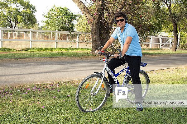 Young man wearing goggles riding bicycle and listening to music.