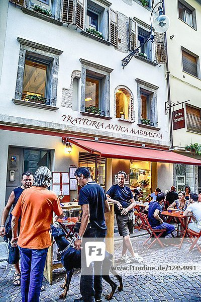 People enjoying a drink and a meal outside the Trattoria Antica Maddalena on Via Pelliccerie in Udine  Italy.