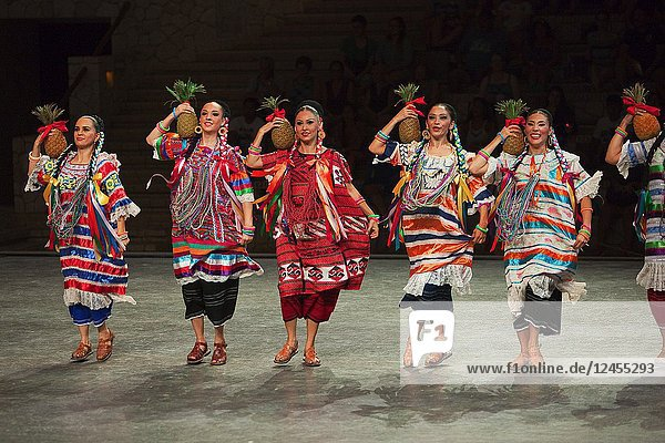 Women during 'Pineaaple Flower' dance at the performance of''Mexico Espectacular''' with traditional dress at the stage  Xcaret  Playa del Carmen  Riviera Maya  Quintana Roo  Mexico  Central America