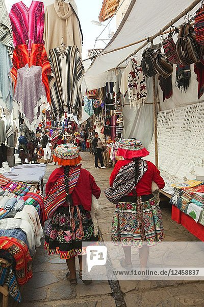Indigeous women in traditional clothing walking at the open-air market in the town center  Pisac  Cusco Region  Urubamba Valley  Peru  South America