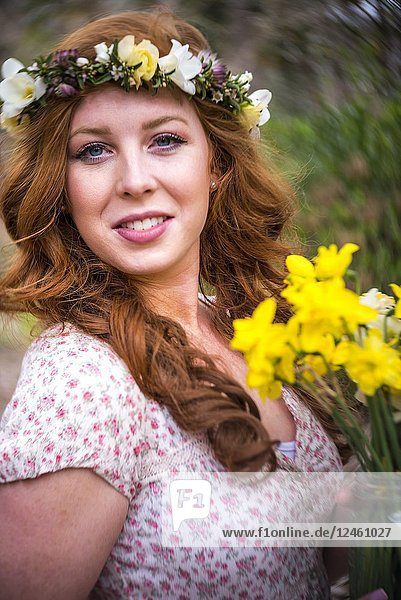 A portrait of a pretty 25 year old redheaded woman smiling at the camera.
