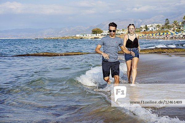 Couple running at beach. In holiday destination Chersonissos  Crete  Greece.
