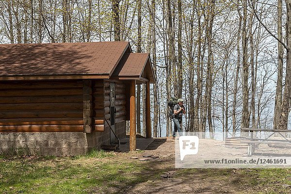 Ontonagon  Michigan - A backpacker arrives at the Whitetail Cabin on the shore of Lake Superior in Porcupine Mountains Wilderness State Park. The park provides primitive backcountry cabins and yurts for hikers throughout the park.