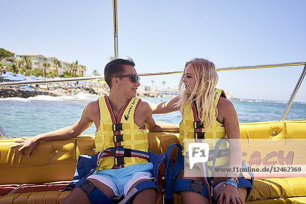 Couple sitting on boat  wearing lifejackets  waiting for parasailing. Chersonissos. Crete  Greece.