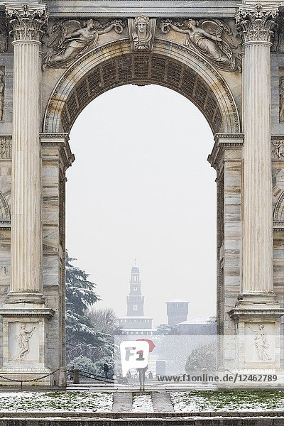 A woman with red umbrella admires the view of Sempione park during a snowfall. Milan  Lombardy  Italy  Europe.