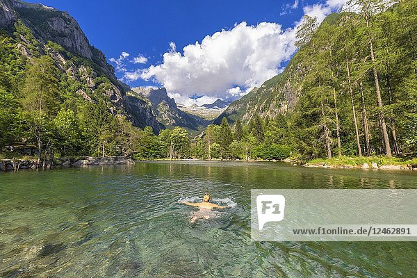 A girl swims in a clear alpine lake. Val di Mello(Mello Valley)  Valmasino  Valtellina  Lombardy  Italy  Europe.