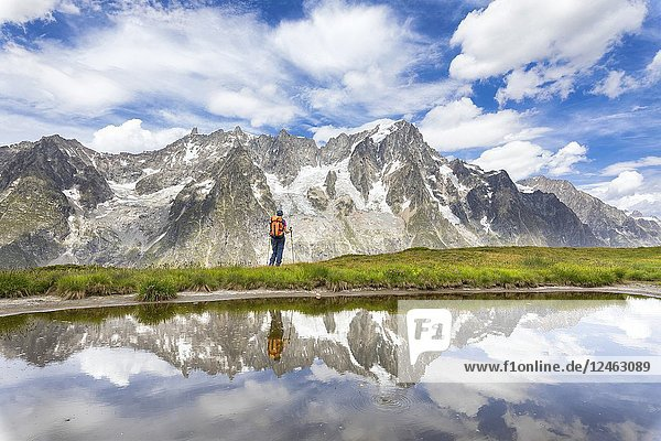 A girl is watching the Grandes Jorasses and the Mont Blanc Massif from the Mont de la Saxe during the Mont Blanc hiking tours (Ferret Valley  Courmayeur  Aosta province  Aosta Valley  Italy  Europe).