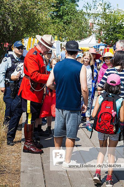 An officer of the Royal Canadian Mounted Police in dress uniform mingling with crowds at the 2018 Steveston Maritime Festival.
