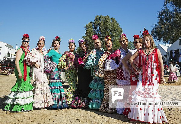 Women wearing beautifully coloured gypsy dresses during the annual Pentecost pilgrimage of El Rocio. Huelva province  Andalusia  Spain.