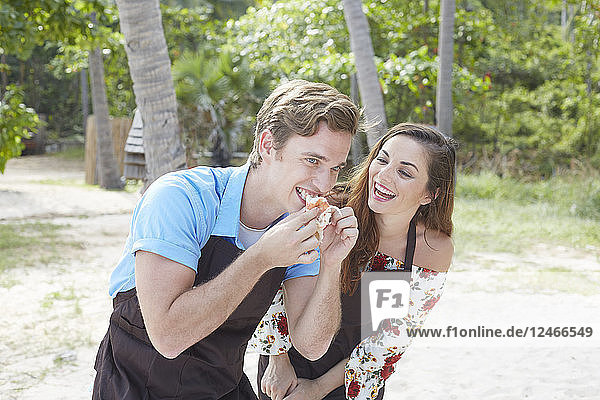 Young man eating on beach with young woman