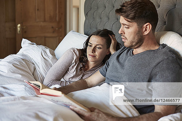 Mid adult married couple reading in bed together.